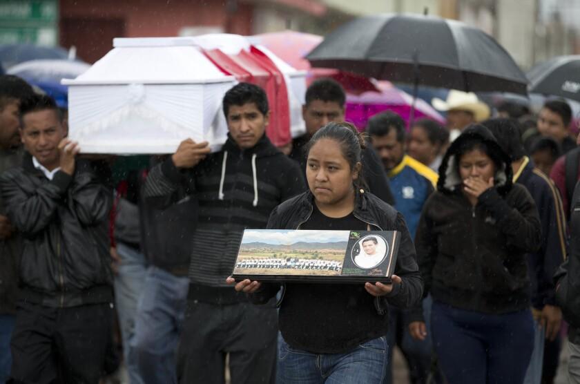 En esta imagen del martes 21 de junio de 2016, una joven camina con una fotografía de Jesús Cadena, que fallecidó el domingo anterior cuando la policía despejaba una autopista, mientras otros cargan el ataúd en Nochixtlán, en el estado de Oaxaca, México. Al menos 8 personas murieran en choques durante el fin de semana entre la policía y maestros en huelga. Los maestros protestaban contra los planes de reformar el sistema educativo del país con evaluaciones federales obligatorias sobre el profesorado. (AP Foto/Eduardo Verdugo)
