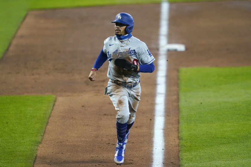 Dodgers' Mookie Betts scores against the Seattle Mariners.