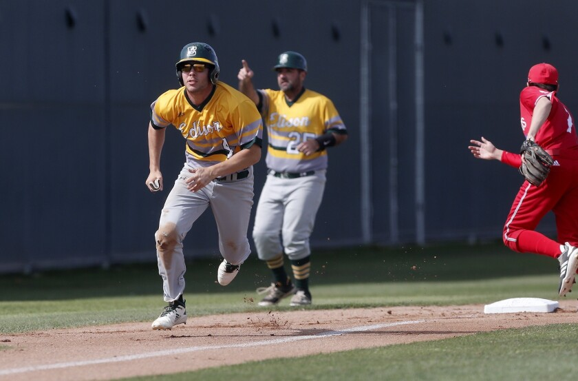 Edison High's Garrett Runyan, left, steals home base after an error by Los Alamitos in the first inn
