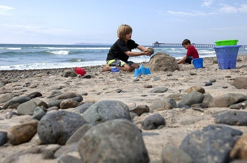 Two pals play with sand amid the rocks on Imperial Beach, where the shore is in need of replenishing, possibly with a U.S. Army Corps of Engineers project to deepen the San Diego Bay entrance.