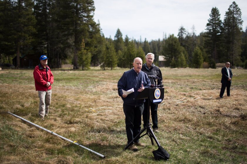 Gov. Jerry Brown speaks during a news conference on mandatory water restrictions Wednesday from an elevation above 7,000 feet in California's Sierra Nevada mountains, which would normally have several feet of snow this time of year.