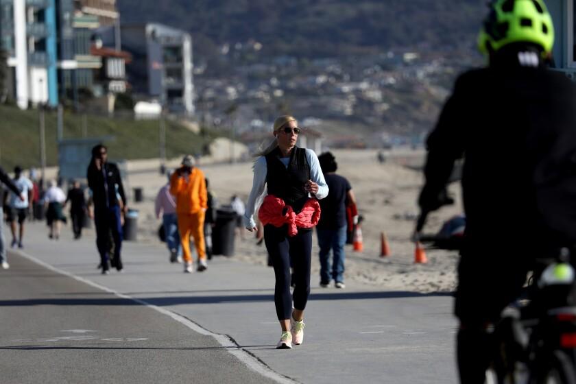 People walk along the boardwalk in Redondo Beach.