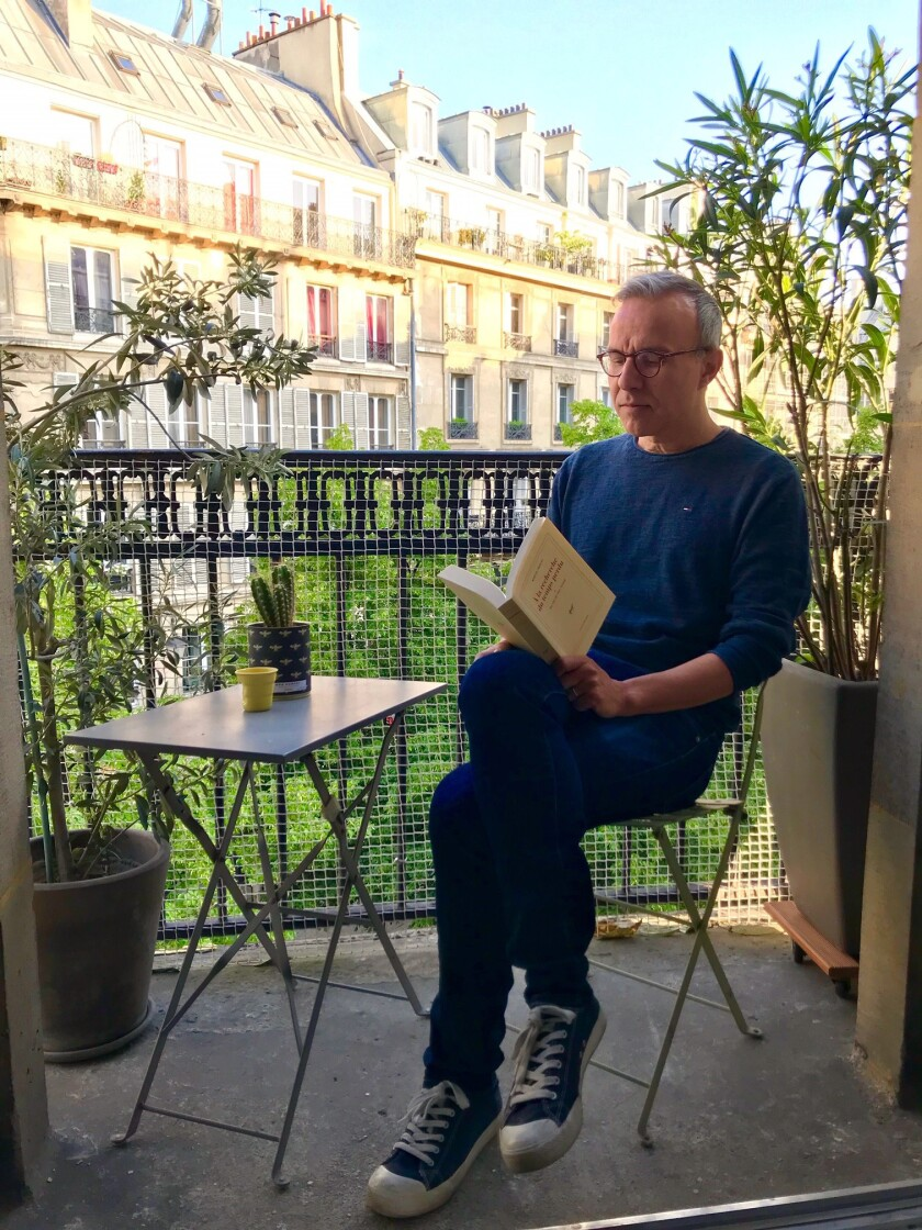 """Philippe Besson, whose latest novel, """"Lie With Me,"""" was translated into English by Molly Ringwald, reads on the balcony of his Paris apartment."""