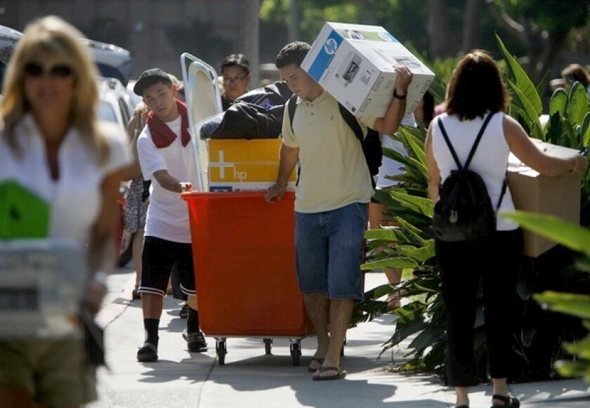 College students with boxes and carts move into their dorm rooms at UCLA.