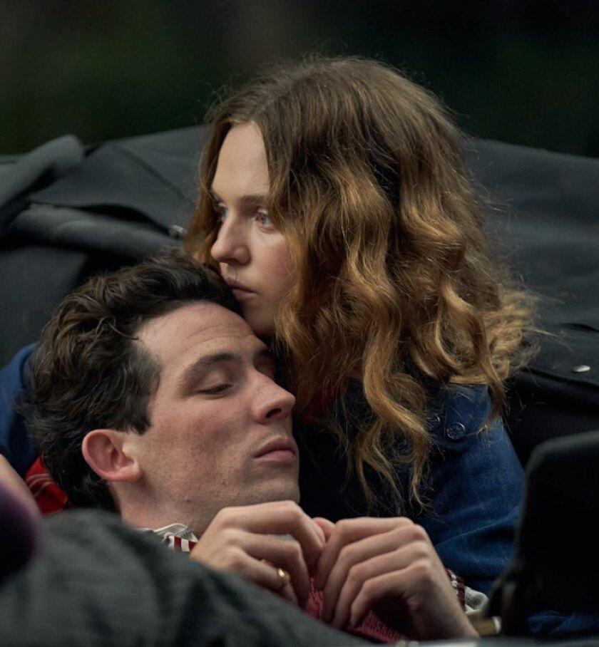 A man leans his head against a woman's shoulder.