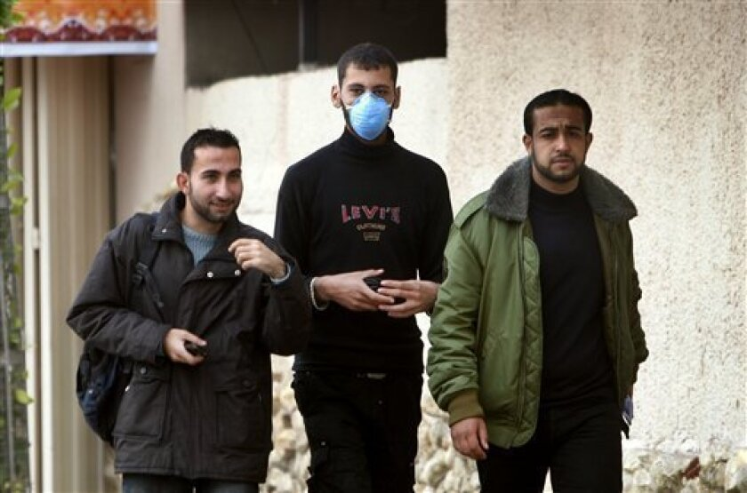 A Palestinian wears a protective face masks against swine flu as he walks with others in Gaza City, Tuesday, Dec. 8, 2009. Israel said Tuesday it is treating five suspected swine flu cases from Gaza in hopes of containing an outbreak of the virus in the blockaded Palestinian territory. Gaza health officials reported their first swine flu cases on Sunday. They say since then three people have died and nine others are hospitalized. (AP Photo/Khalil Hamra)