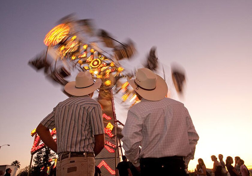 Fernando Molina, left, and Carlos Mora, both of Tulare, watch the Zipper ride at the Tulare County Fair. The Zipper formerly operated at Michael Jackson's Neverland Ranch and now is owned by Helm and Sons, which operates carnival rides.