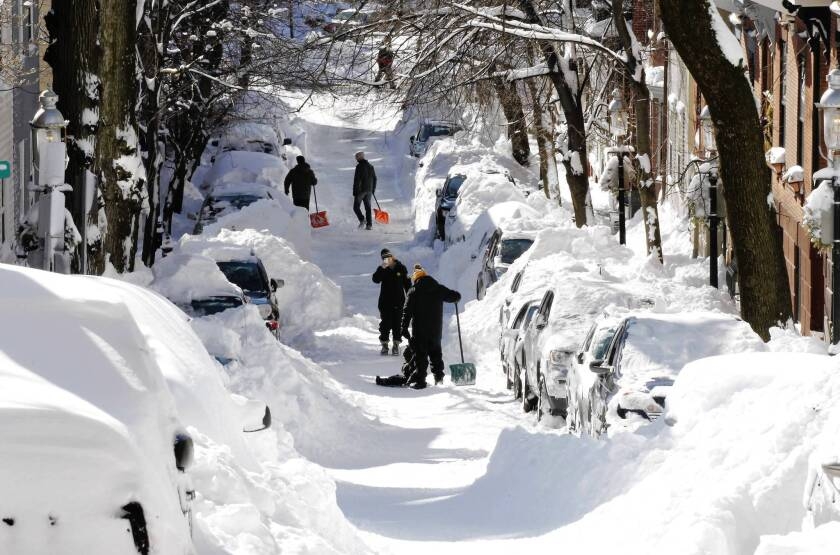 Shovelers pause while digging out their cars on a street in Boston. Life was slowly getting back to normal after a major weekend blizzard, but power remained out and roads blocked in many parts of the Northeast.