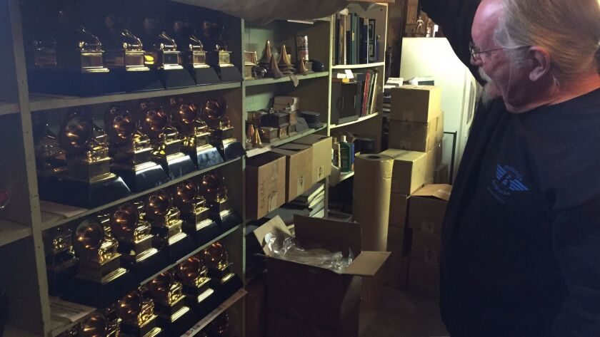 Billings lifts a curtain to reveal shelves of so-called `stunt Grammys' which are given to the artis