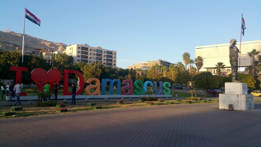 "Pedestrians lounge near the newly installed ""I love Damascus"" sign in Damascus, Syria, on Oct. 31."