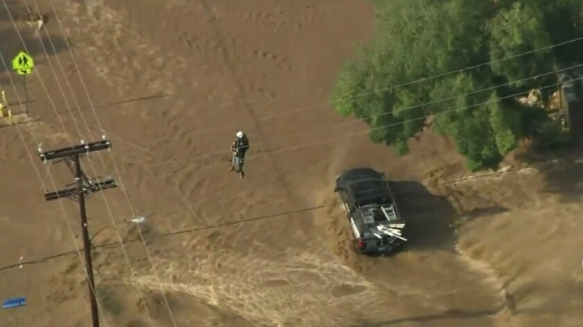 A driver who became trapped in a flooded roadway in Acton is airlifted to safety.