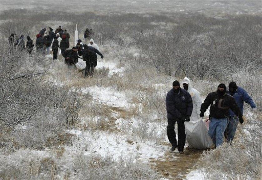 Police and forensic workers carry two bodies of people killed after a drug gang kidnapped and killed six people in Villa Ahumada, on the outskirts of Ciudad Juarez, northern Mexico, Tuesday, Feb. 10, 2009. The violence started when gunmen kidnapped nine alleged members of a rival drug gang and later executed six of them, prompting a series of gunbattles with Mexican Army soldiers that left 15 others dead.(AP Photo)