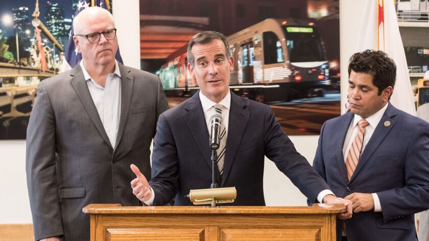 Los Angeles Mayor Eric Garcetti criticizes the GOP tax bill, flanked by Rep. Jimmy Gomez, right, and House Democratic Caucus Chairman Joe Crowley, left, during news conference at Metro headquarters.