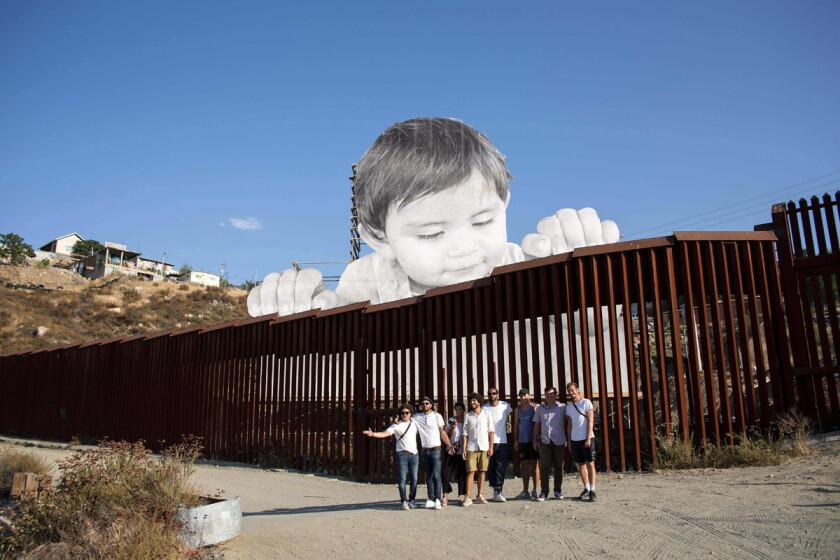 French artist JR poses for a group photo near his artwork on the US-Mexico border in Tecate, California. (Getty Images)