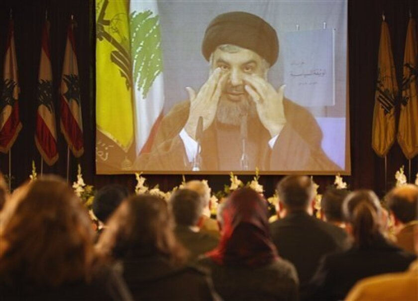 Hezbollah leader Sheik Hassan Nasrallah, is seen speaking via a video link as journalists listen to him during a press conference in which he read the group's new political manifesto, the second since Hezbollah was born in the early 1980s, in the southern suburb of Beirut, Lebanon, on Monday Nov. 3