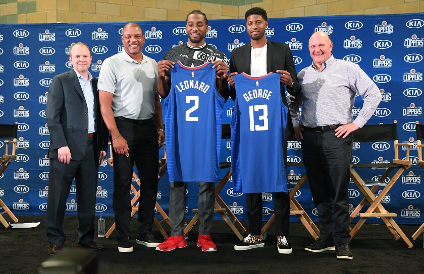 From left, Clippers president of Basketball Operations Lawrence Frank, head coach Doc Rivers, new players Kawhi Leonard  and Paul George and owner Steve Balmer pose for a photo at Green Meadows Recreation Center during a press conference in Los Angeles on Wednesday.