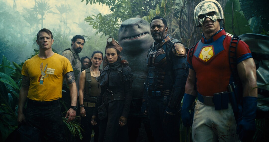 Seven people in combat gear and an anthropomorphic shark standing in a jungle
