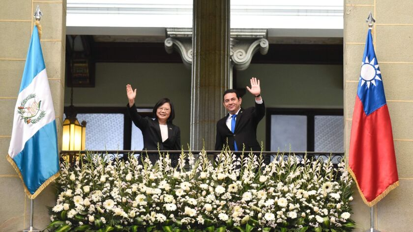 Taiwan's President Tsai Ing-wen and Guatemalan President Jimmy Morales wave from a balcony at the Culture Palace in Guatemala City on Jan. 11, 2017.