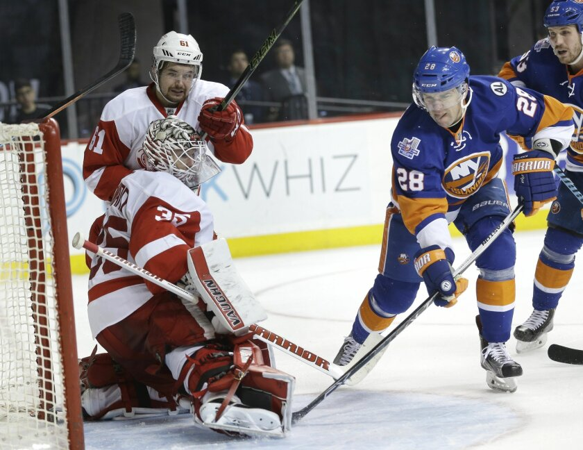 New York Islanders' Marek Zidlicky, right, scores past Detroit Red Wings goalie Jimmy Howard, bottom left, and Xavier Ouellet during the second period of an NHL hockey game, Monday, Feb. 15, 2016, in New York. (AP Photo/Seth Wenig)