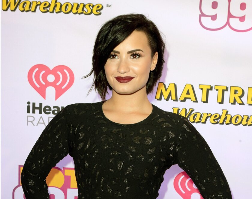"""FILE - In this Dec. 15, 2014 file photo, Demi Lovato poses for photographers backstage during the Hot 99.5 Jingle Ball in Washington D.C. Robert Rodriguez had been waiting for a chance to work with Lovato since she auditioned for a role in his 2003 movie """"Spy Kids 3-D: Game Over."""" The El Rey Network creator and executive producer of its TV series """"From Dusk Till Dawn,"""" spoke to reporters Thursday, July 30, 2015, as part of a TV Critics annual summer press tour. (Photo by Owen Sweeney/Invision/AP, File)"""