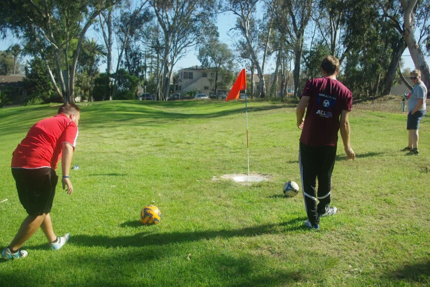 Footgolfers line up their putts during a round at Balboa Park 9 Golf Course last year.