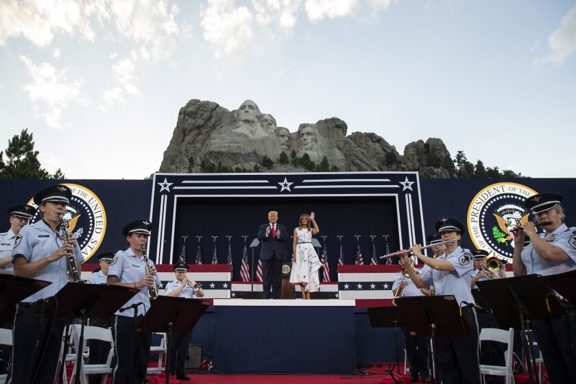 President Donald Trump, accompanied by First Lady Melania Trump, stand during a ceremony at Mount Rushmore National Memorial.