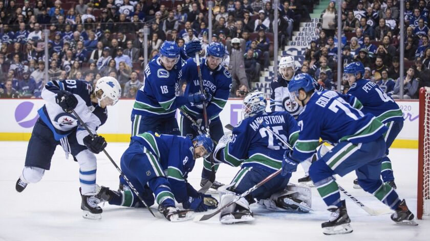 Winnipeg Jets' Kyle Connor (81) digs for the puck under Vancouver Canucks' Chris Tanev (8) in front