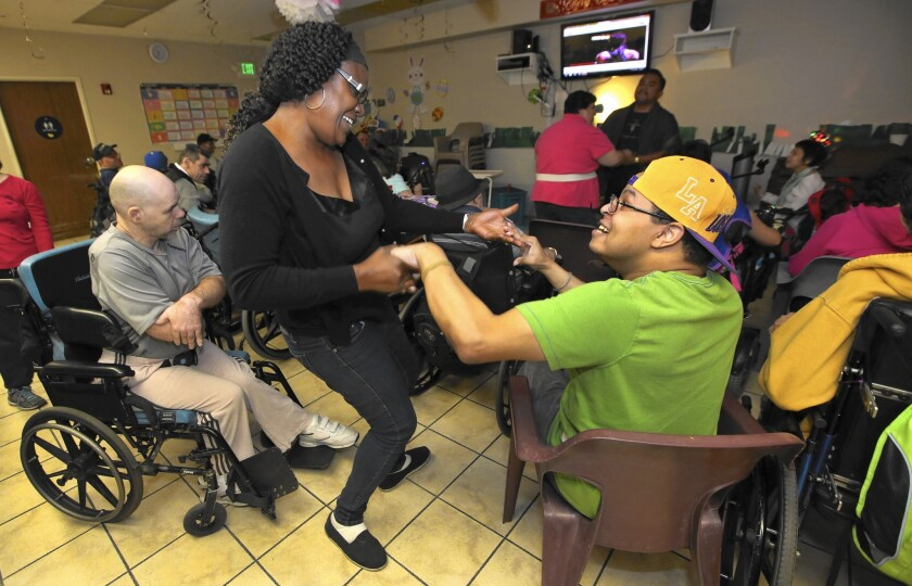 Alice Jackson, an aide at the nonprofit Valley Village adult day care center in Winnetka, dances with a client. The nonprofit supports the idea of boosting the minimum wage but estimates it faces a 31% bump in its payroll if wages increase to $13.25.
