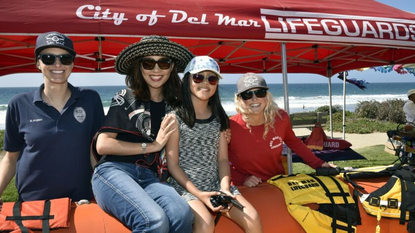 Del Mar lifeguard Claire O'Leary, Minchi Kim with Angelina, lifeguard Lauren Humann