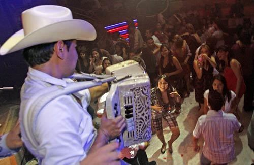 Alfredo Madrigal, a member of Herederos de la Frontera, plays accordion for admiring fans at the Baby Rock club in Tijuana. His group specializes in traditional Norteño-style ballads.