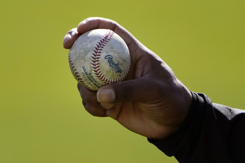 FILE - A Colorado Rockies pitcher shows his grip to a teammate during a spring training baseball workout in Scottsdale, Ariz., in this Wednesday, Feb. 24, 2021, file photo. Pitchers will be ejected and suspended for 10 games for using illegal foreign substances to doctor baseballs in a crackdown by Major League Baseball that will start June 21. The commissioner's office, responding to record strikeouts and a league batting average at a more than half-century low, said Tuesday, June 15, 2021, that major and minor league umpires will start regular checks of all pitchers, even if opposing managers don't request inspections. (AP Photo/Jae C. Hong, File)