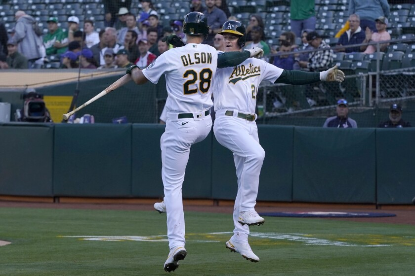 Oakland Athletics' Matt Chapman, right, is congratulated by Matt Olson after hitting a home run against the Texas Rangers during the first inning of a baseball game in Oakland, Calif., Tuesday, June 29, 2021. (AP Photo/Jeff Chiu)