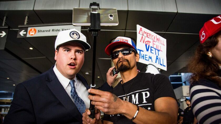 Trump supporters Omar Navarro, left, and Harim Uzziel live-stream their counter-protest at Los Angeles International Airport of the executive order by President Trump banning immigrants from seven majority-Muslim countries.