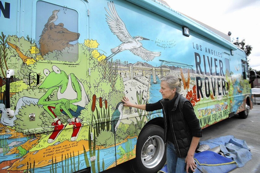 """Starting in May, the River Rover, festooned with splashy exterior renderings of riverscapes past, present and future — and amphibian mascot """"Froggy"""" — will become a familiar sight at the 120 schools within a mile of the L.A. river. Above, artist Christian Kasperkovitz next to artwork she designed on the Rover's exterior."""