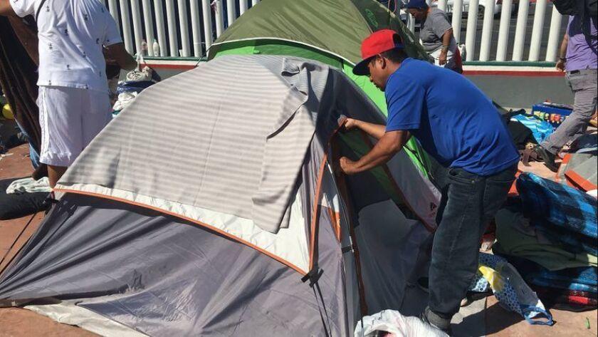 Un grupo de voluntarios desmantelan uno de los campamentos de los miembros de las caravanas migrantes en Tijuana, luego de que el gobierno local les retiró su apoyo.