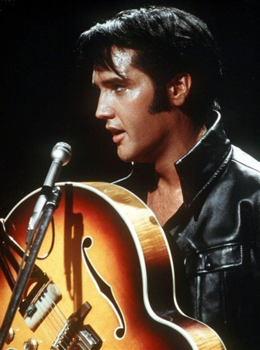 In this 1968 file photo, Elvis Presley holds his semi-acoustic guitar during a concert. (AP Photo, file)