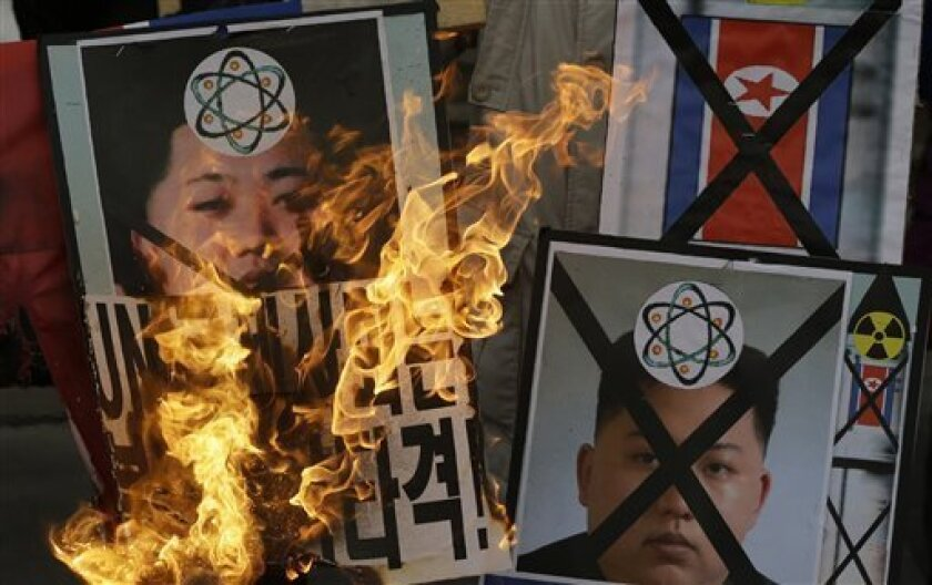 South Korean protesters burn the pictures of North Korean leader Kim Jong Un during an anti-North Korea rally following a nuclear test conducted by North Korea, in Seoul, South Korea, Tuesday, Feb. 12, 2013. North Korea said it successfully detonated a miniaturized nuclear device at a northeastern