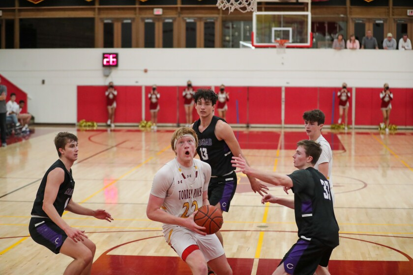 Otto Landrum of Torrey Pines drives in for a basket against Carlsbad on Friday night.