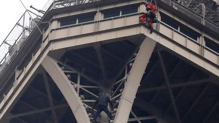 A rescue worker, top in red, hangs from the Eiffel Tower while a climber is seen below him between t