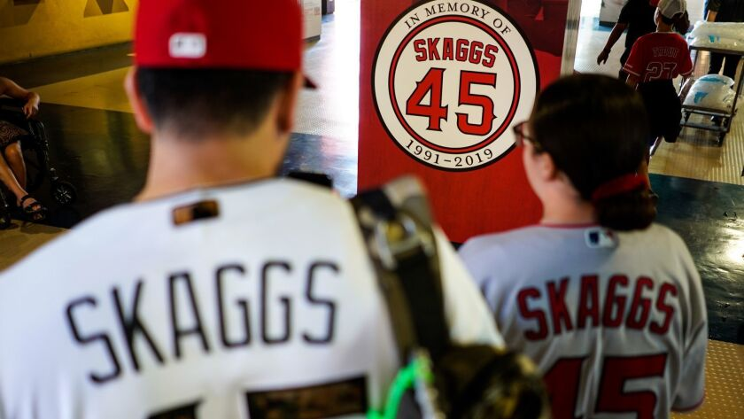 David Palacios, 40, and his daughter Emma, 15, of Covina take pictures of a marker in memory of Tyler Skaggs before the start of the Angels game Friday night.
