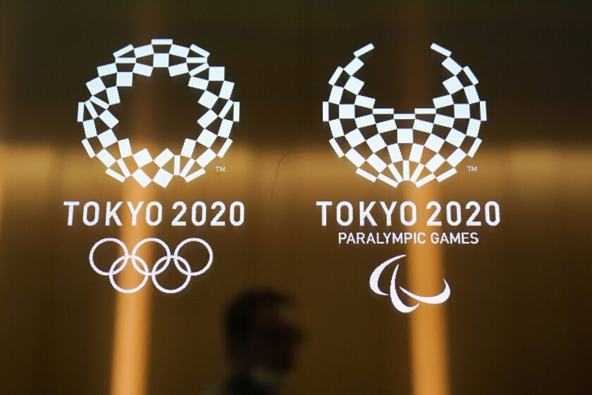 In this June 11, 2019, file photo, a man walks past the logos of the Tokyo 2020 Olympics and Paralympics in Tokyo.