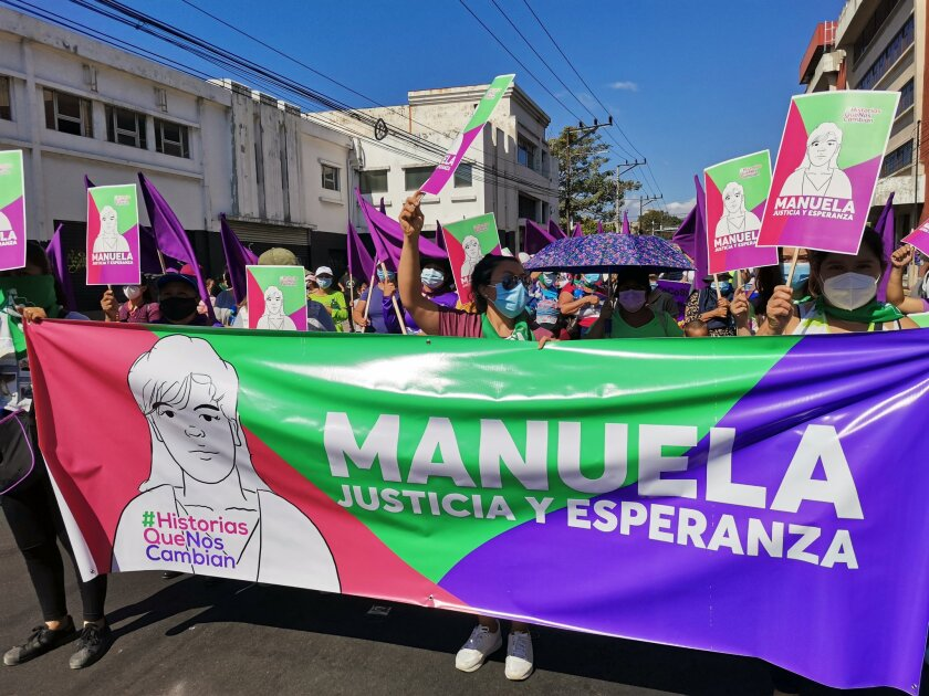 Marchers carry a banner with an image of Manuela.