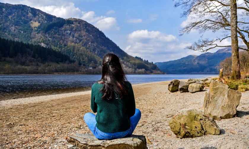View from behind of a woman sitting on a rock looking at a lake