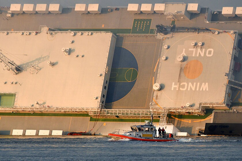 A U.S. Coast Guard boat rides in front of a cargo ship that overturned in St. Simons Sound near the Port of Brunswick in Georgia