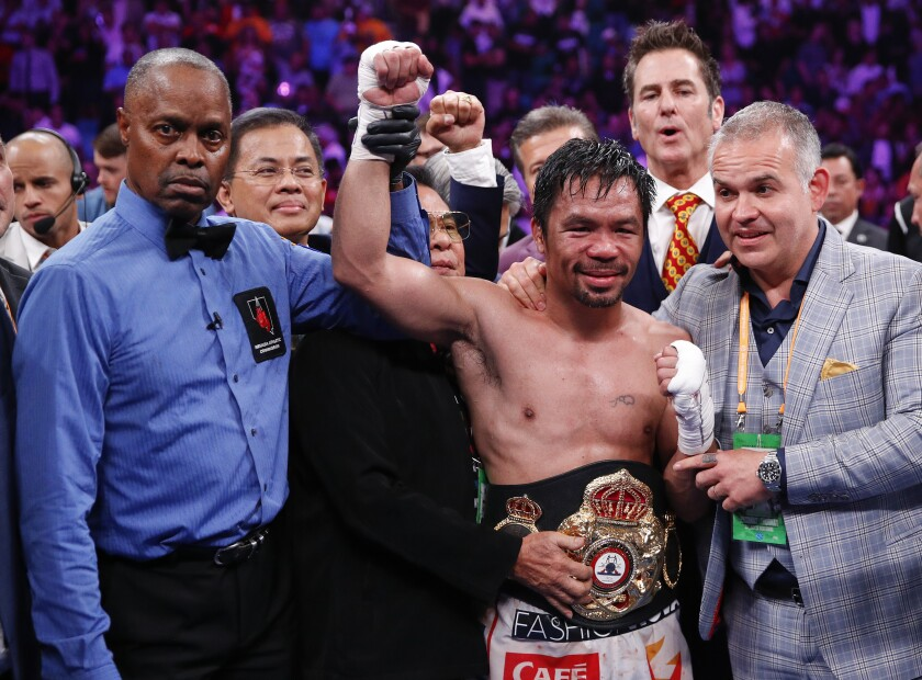 Manny Pacquiao, center, celebrates as referee Kenny Bayless holds up his hand, signaling his victory.