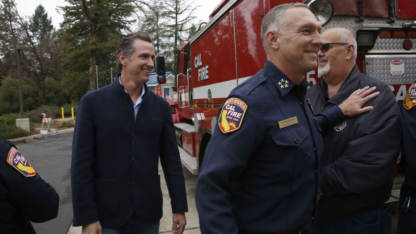 Gov. Gavin Newsom is escorted by Thom Porter, right, to the CalFire Colfax Station in Northern California on Jan. 8. Newsom appointed Porter as director of the Department of Forestry and Fire Protection. He had been serving as interim director.