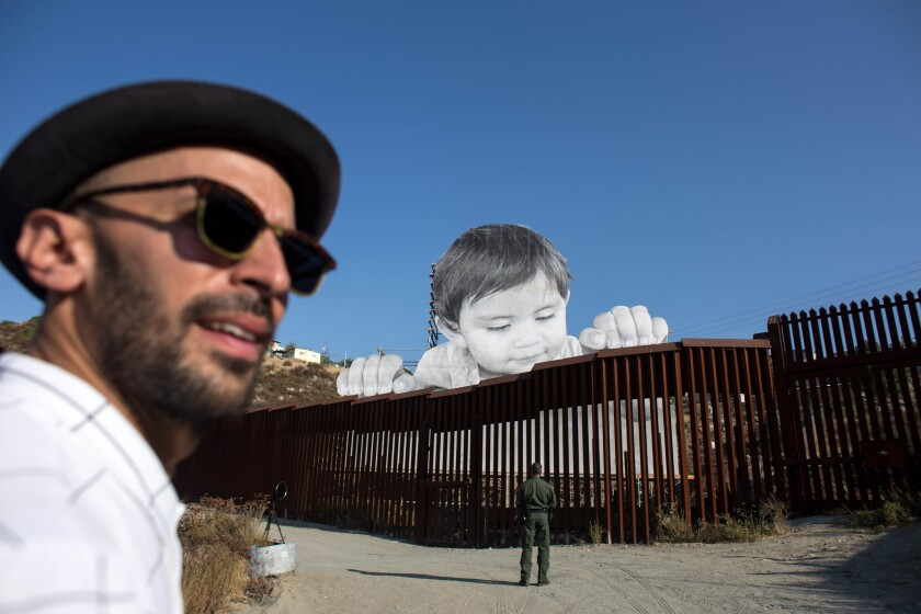 The artist known as JR is pictured near his installation on the US-Mexico border in Tecate, Calif.