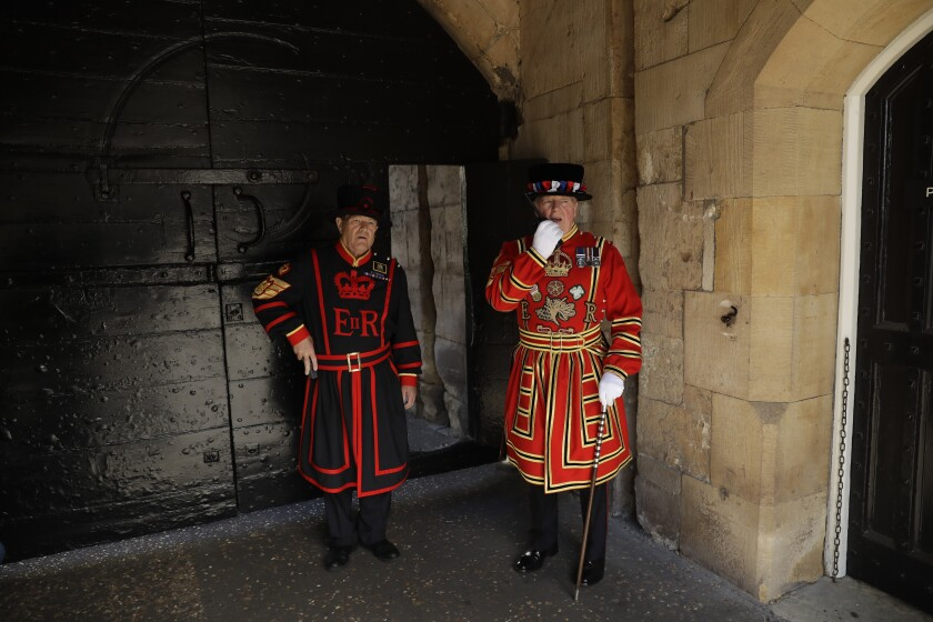 Chief Yeoman Warder Peter McGowran, right, speaks on a radio flanked by Yeoman Gaoler Jim Duncan as they stand next to the gates at the main entrance before opening to visitors at the Tower of London, in London, Friday, July 10, 2020. The Tower of London reopened to visitors Friday as the British government continues to relax its coronavirus restrictions. (AP Photo/Matt Dunham)