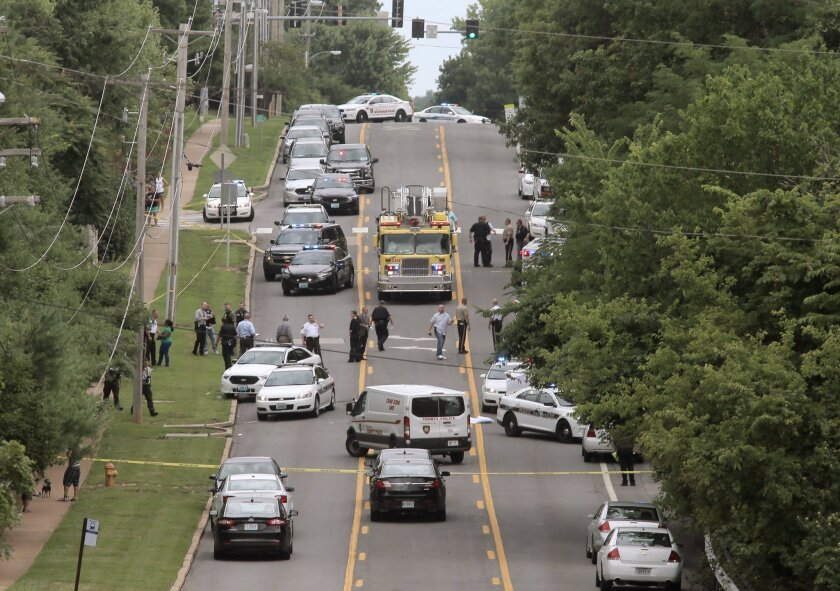 Police investigate a scene in Ballwin, Mo., Friday, July 8, 2016, after a Ballwin police officer was shot during a confrontation with a man on a street.