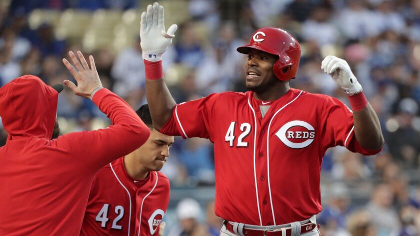 LOS ANGELES, CA - APRIL 15, 2019: Cincinnati Reds Yasiel Puig gets high-fives at the dugout after hi
